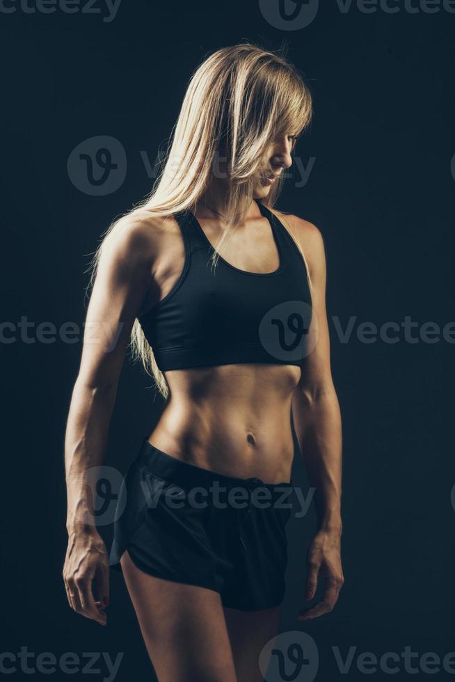 Retrato de mujer deportiva vistiendo ropa deportiva negra sobre oscuro foto