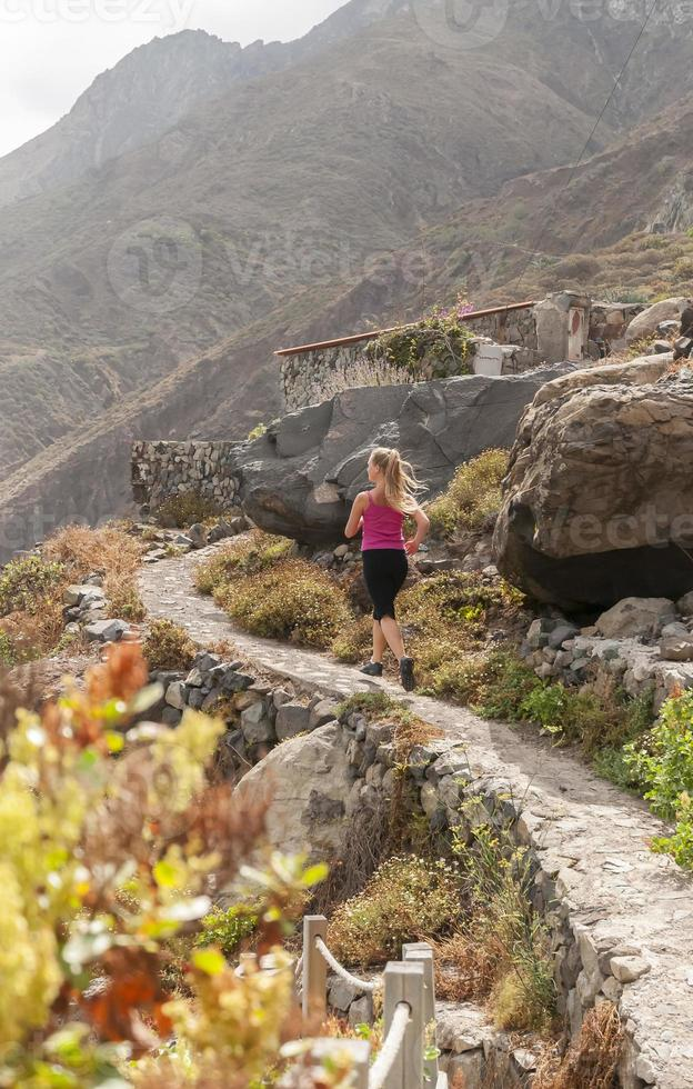 Fitness. Young woman running on a mountain road photo