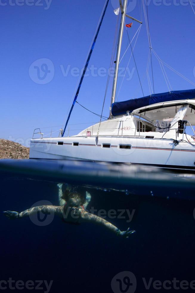 Chica buceando bajo el agua con catamarán arriba foto