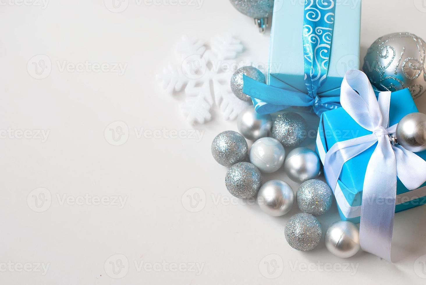 Bolas de Navidad de plata y regalos en mesa de madera foto