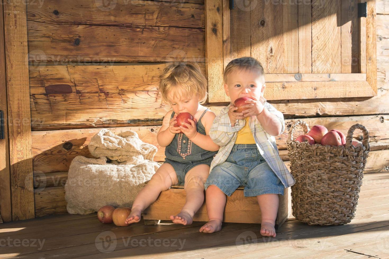 Niña y niño sentado y comiendo manzanas foto