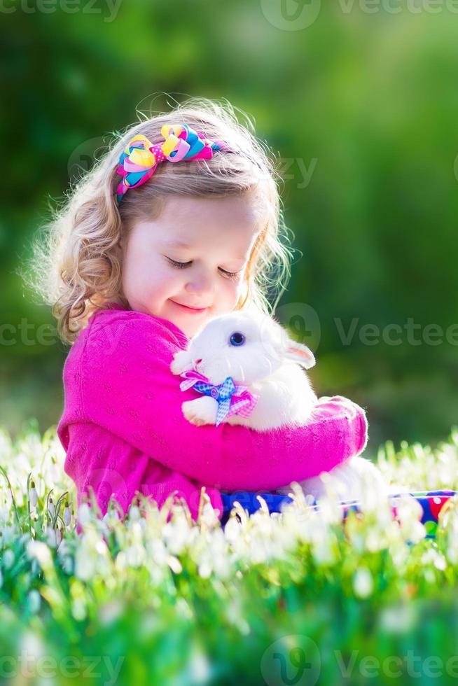 hermosa niña jugando con un conejo foto