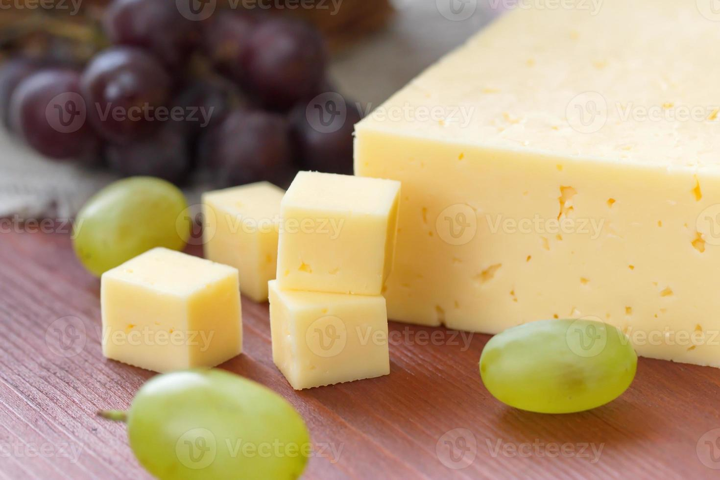 Cheese and grapes on the table photo