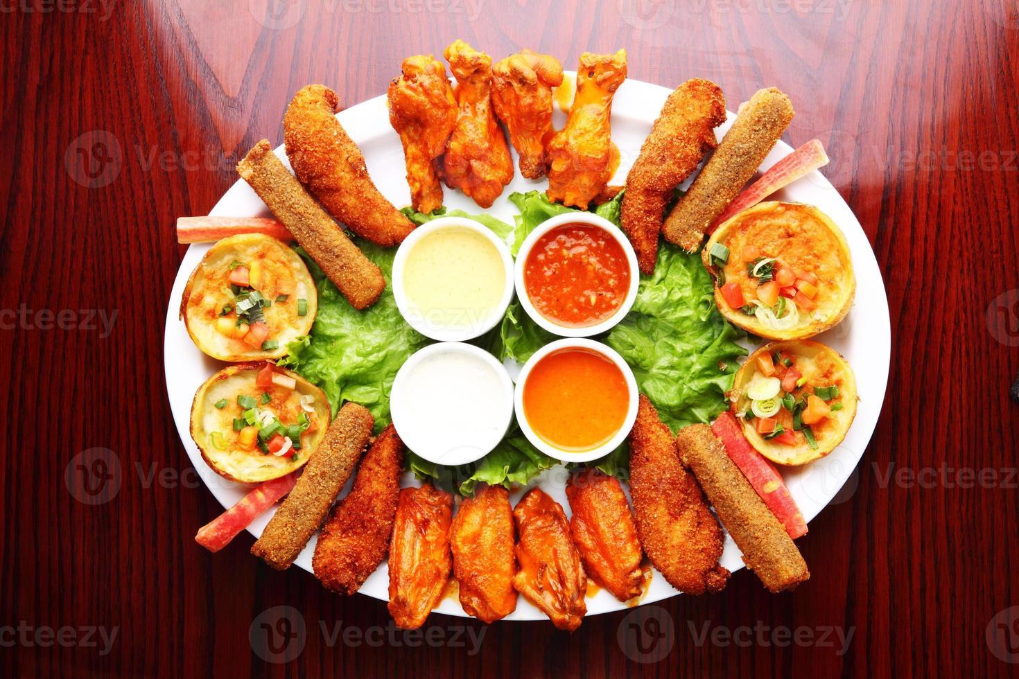 plato de aperitivo alitas de pollo a la brasa, pieles de patata foto