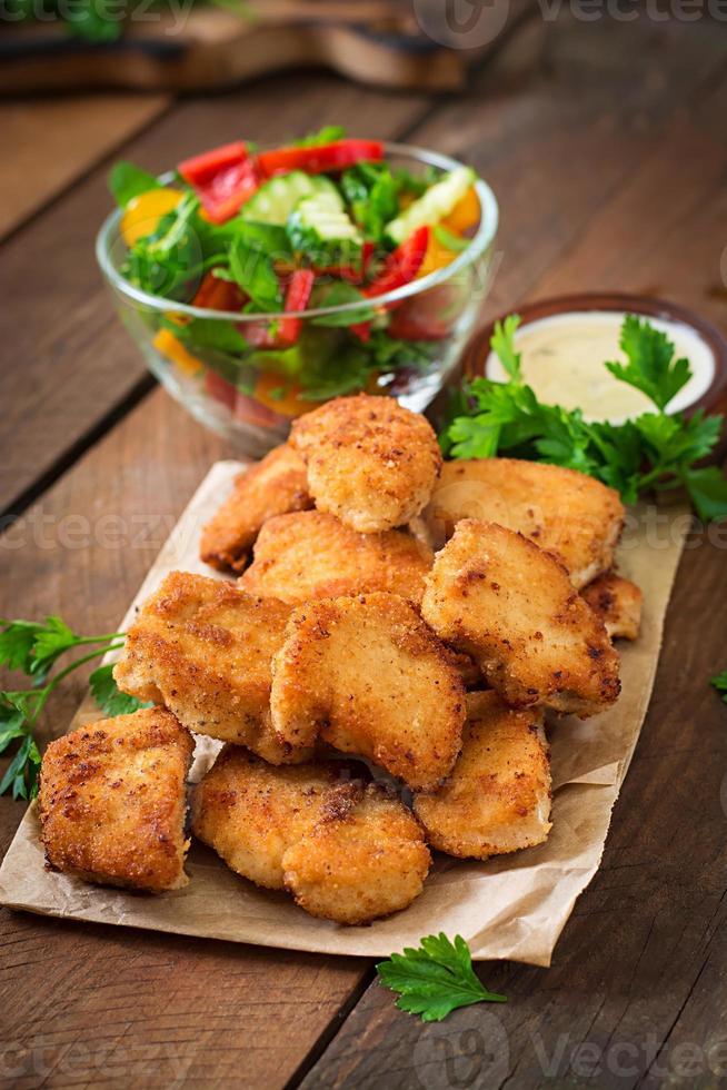 nuggets de pollo y salsa sobre un fondo de madera foto