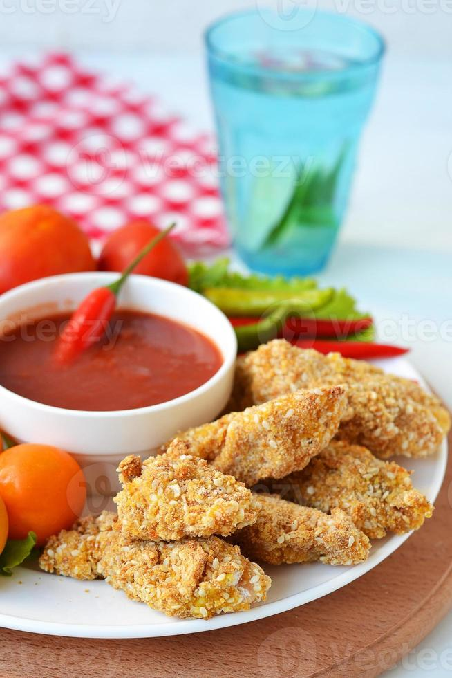 Chicken nuggets with tomato sauce photo