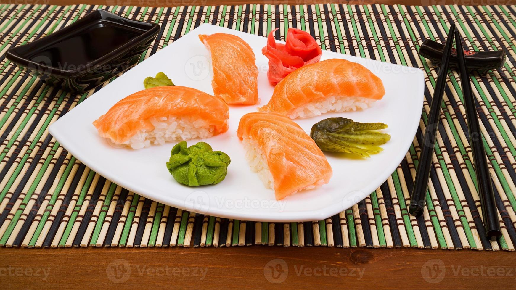 syake di sushi sul piatto quadrato bianco con bastoncini neri foto