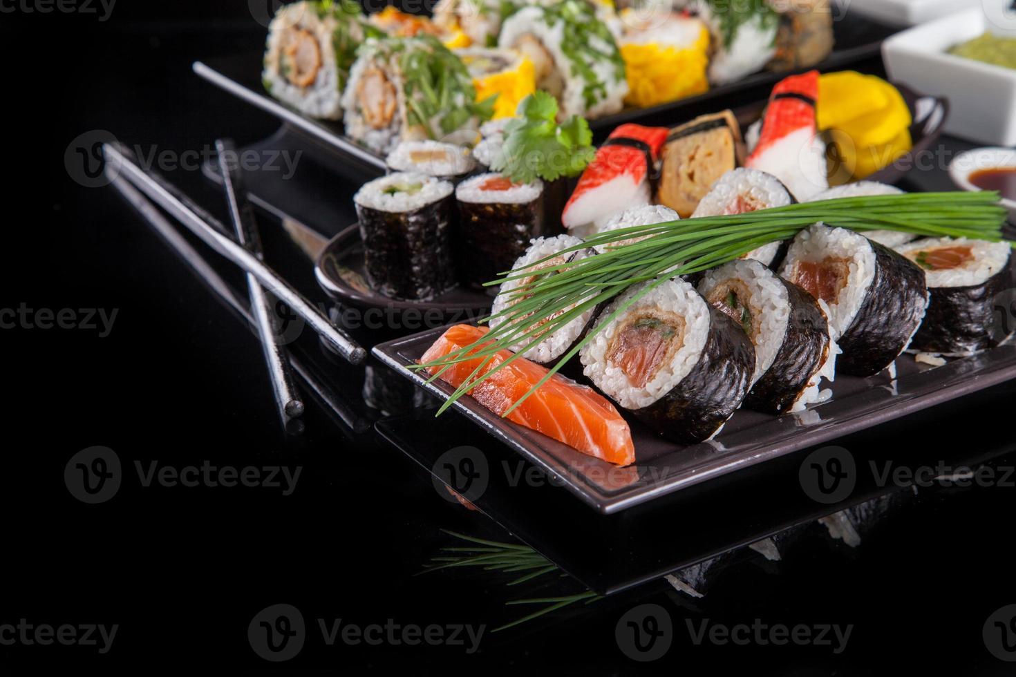 deliciosas piezas de sushi sobre fondo negro foto