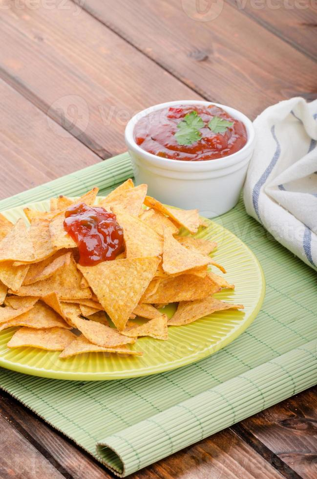 Tortilla chips with spicy tomato salsa photo