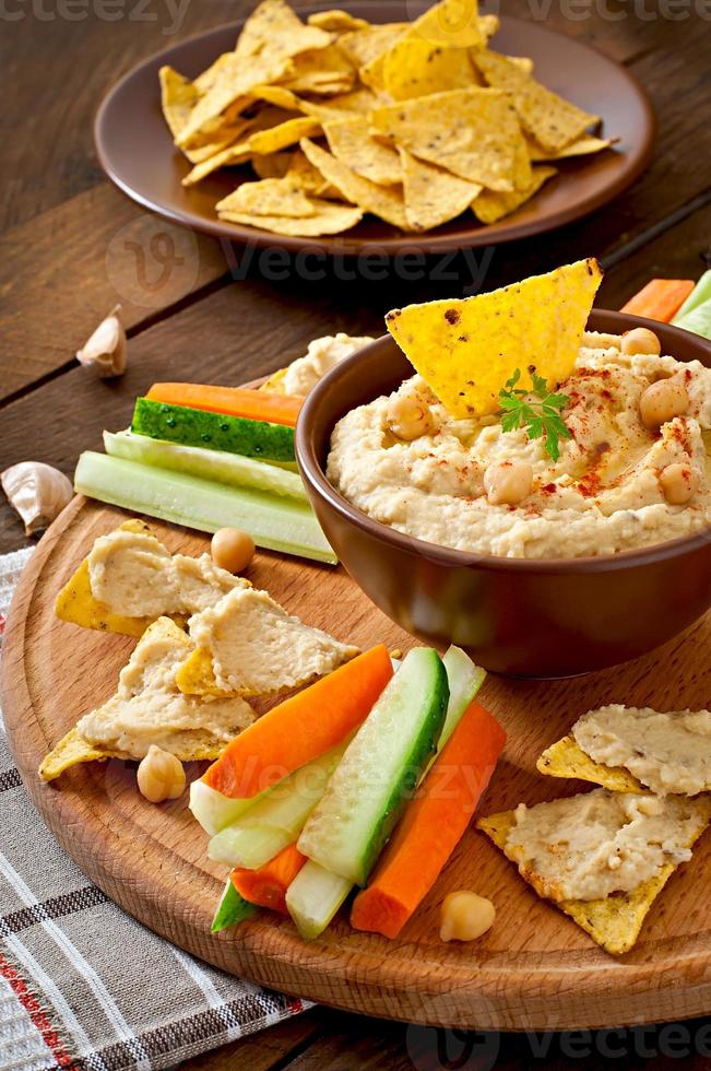 Healthy homemade hummus with vegetables, olive oil and pita chips photo