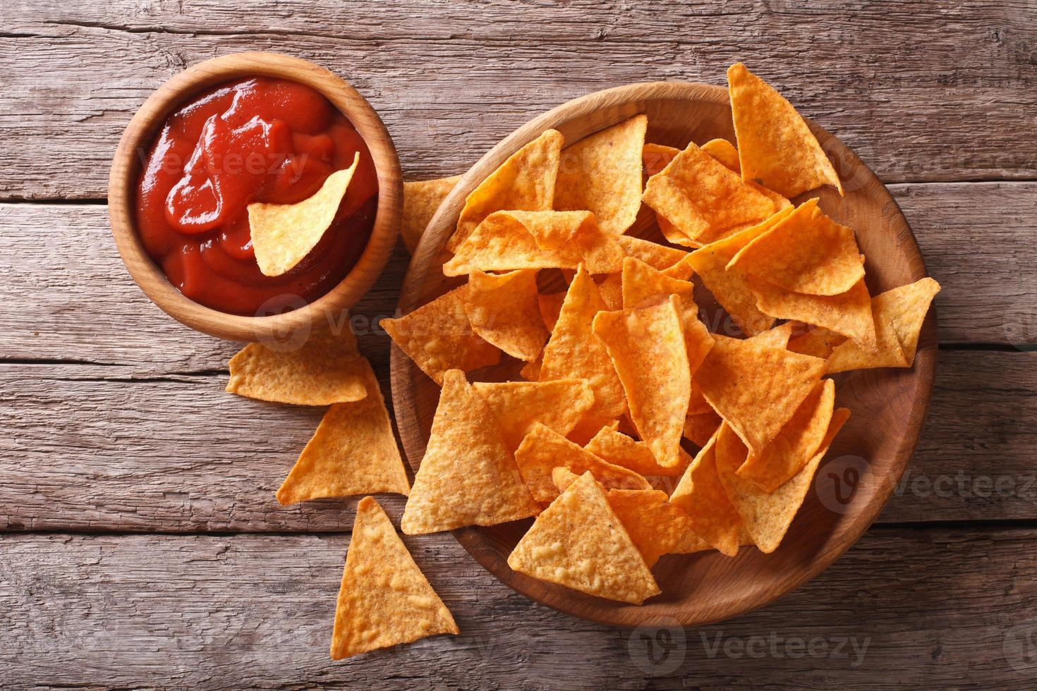 Nachos corn chips with spicy sauce. Horizontal top view photo