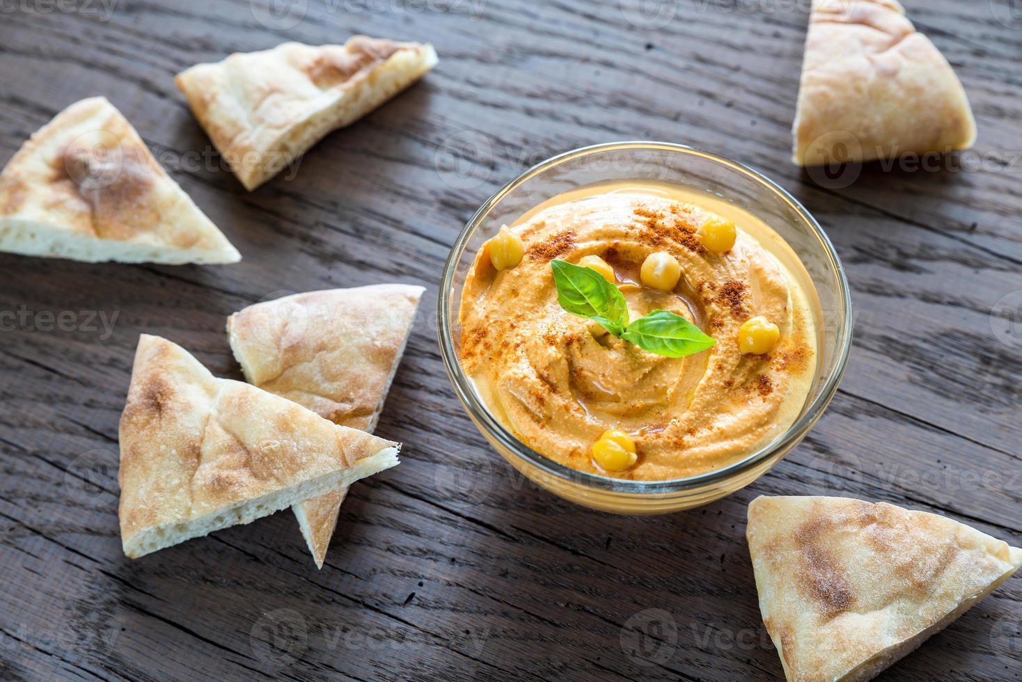 tazón de hummus con rodajas de pita foto