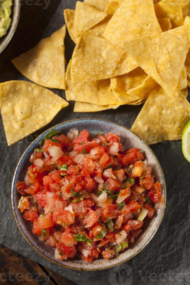 Tazón casero de salsa pico de gallo con nachos al lado foto