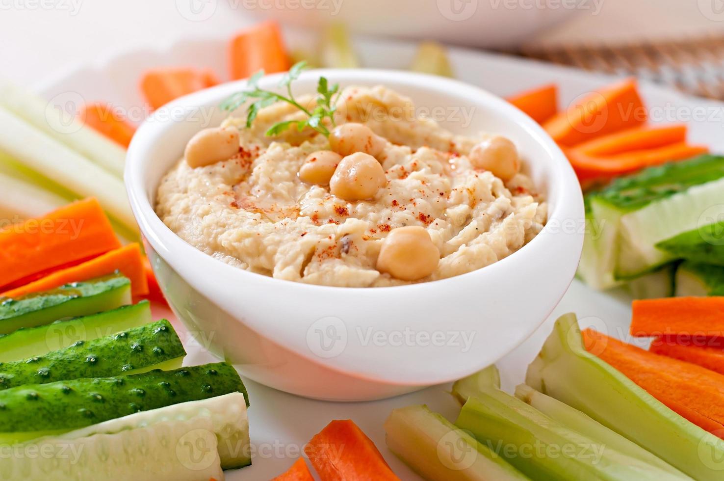 hummus casero saludable con verduras, aceite de oliva y chips de pita foto