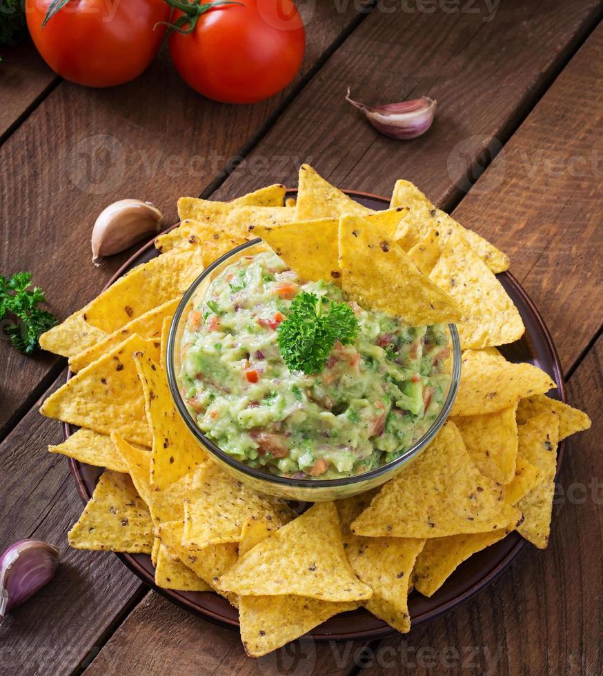aguacate guacamole, lima, tomate, cebolla y cilantro, servido con nachos foto