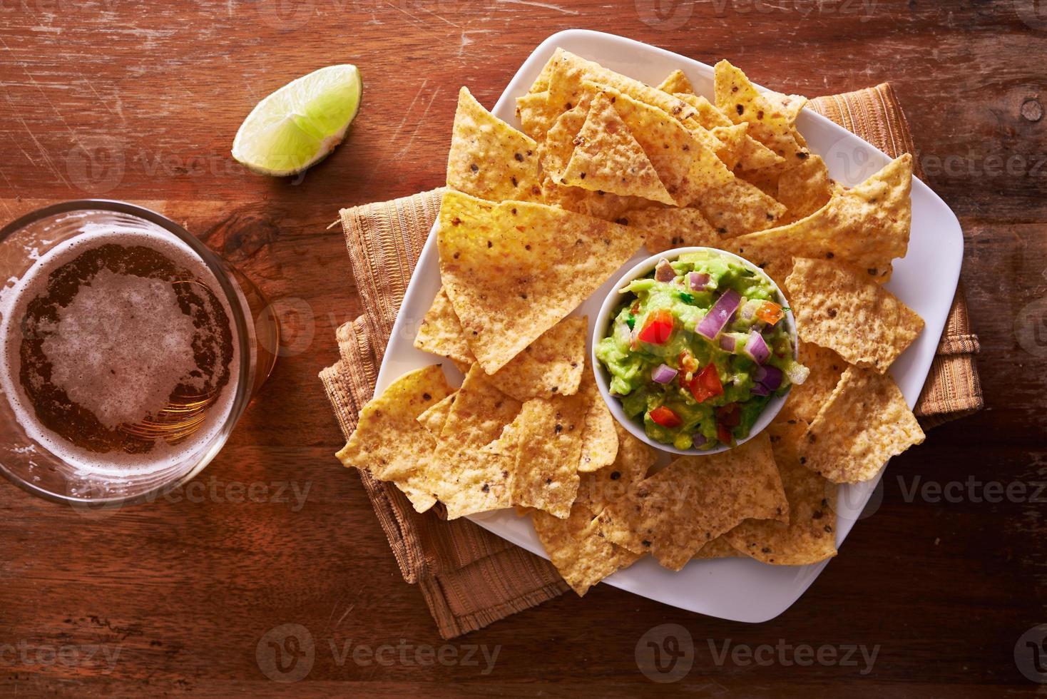 chips de tortilla con guacamole y cerveza foto