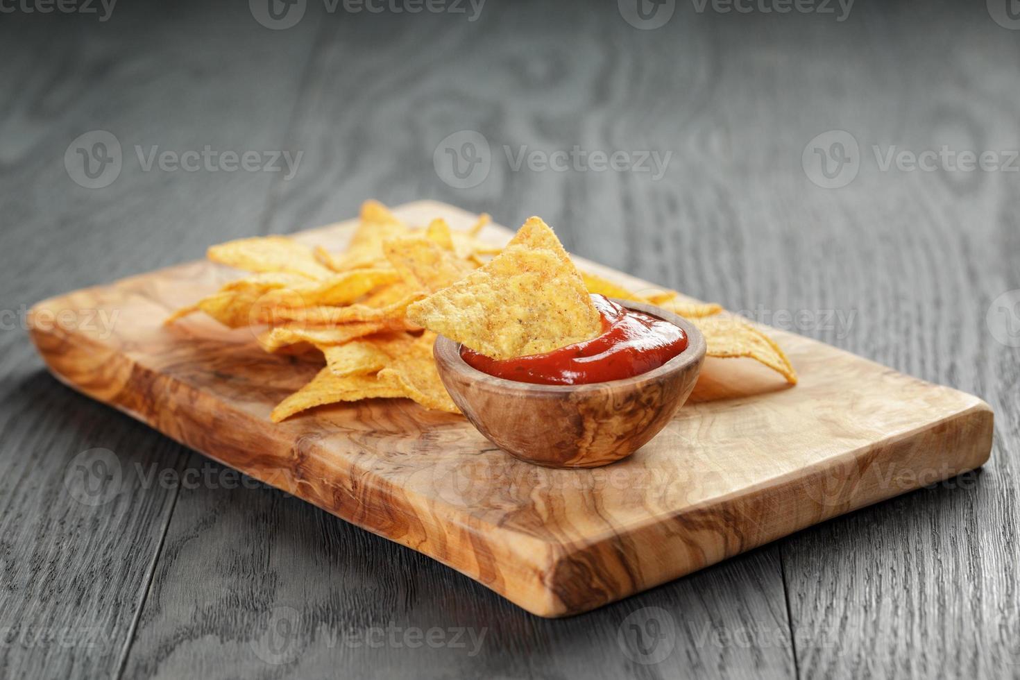 Montón de tortilla chips en tablero de oliva en la mesa de madera foto