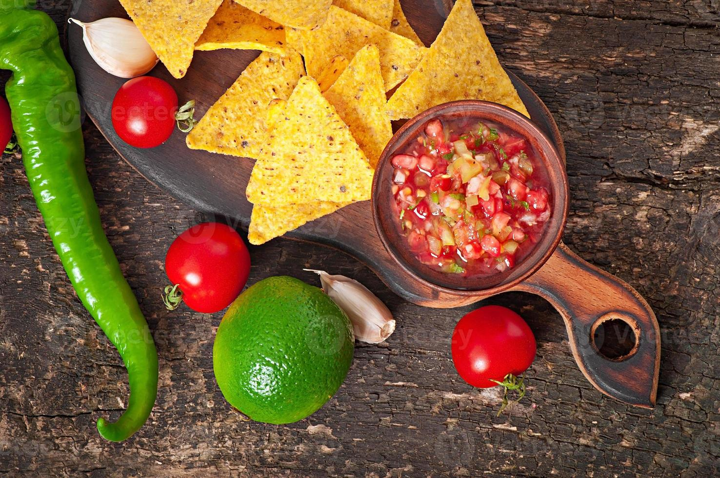 Mexican nacho chips and salsa dip in bowl photo