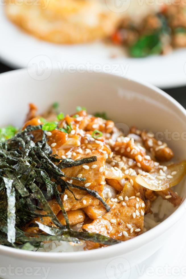 cerdo frito y arroz con algas encima foto