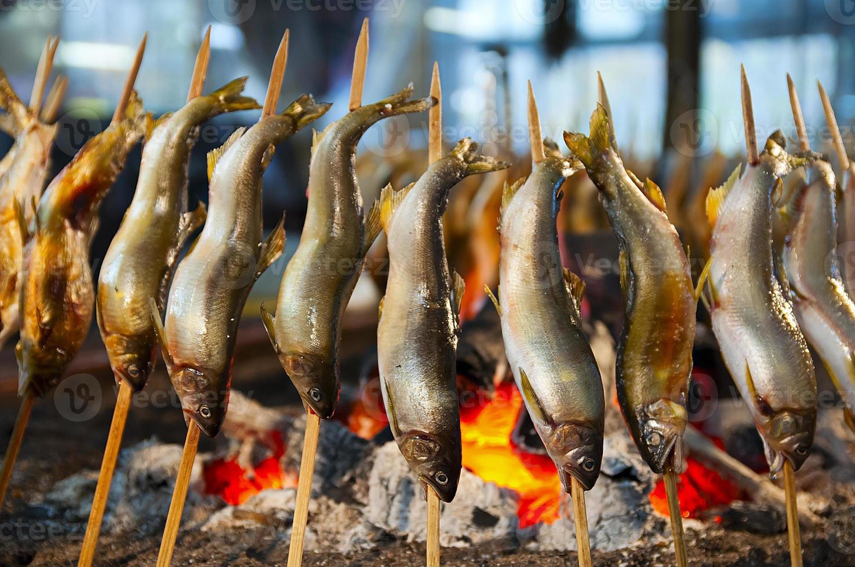 comida japonesa en la calle, parrilla de brochetas de pescado de agua dulce. foto