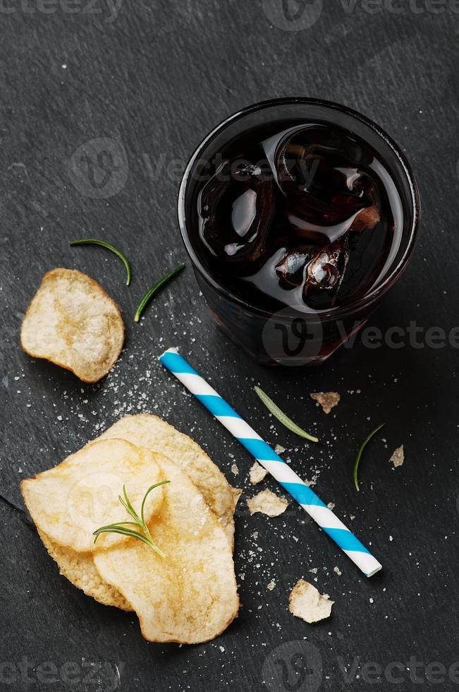 papas fritas y un vaso de cola sobre la mesa foto