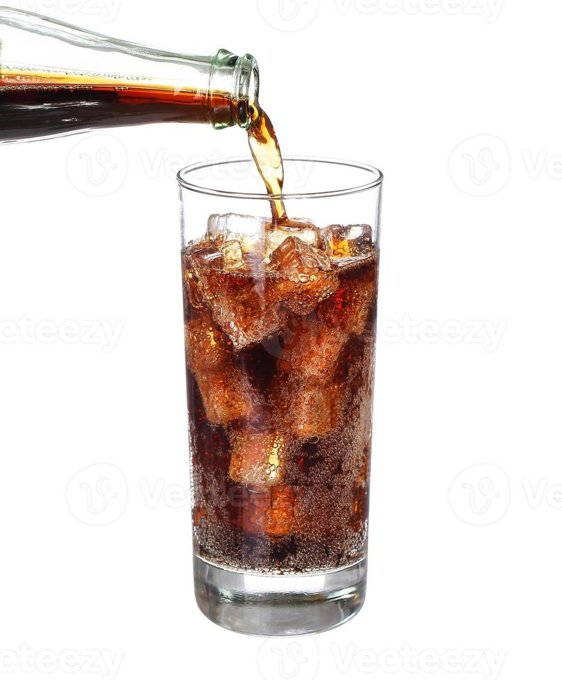 fles coke gieten in drank glas met ijsblokjes geïsoleerd foto