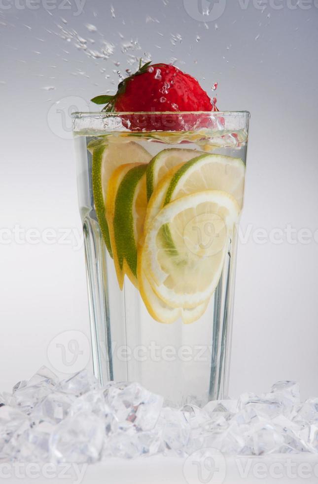 Vaso de bebida con cubitos de hielo y frutas en blanco foto