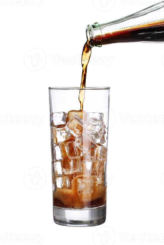 Coca-Cola vertiendo botella en vaso con cubitos de hielo aislado foto