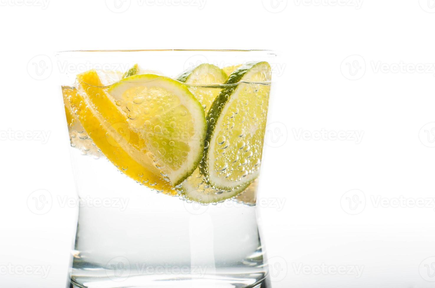 vaso de agua con rodaja de limón foto