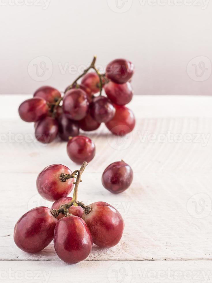 uvas rojas en mesa de madera foto