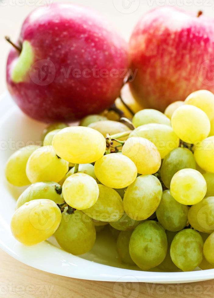 Manzana y uva en plato, fondo blanco. foto