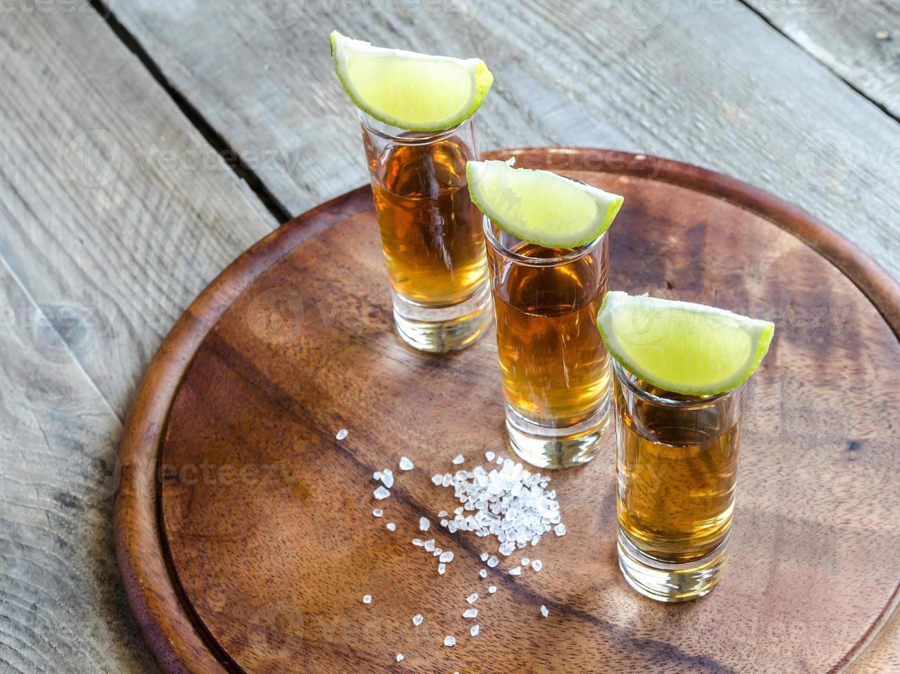 vasos de tequila sobre la plancha de madera foto