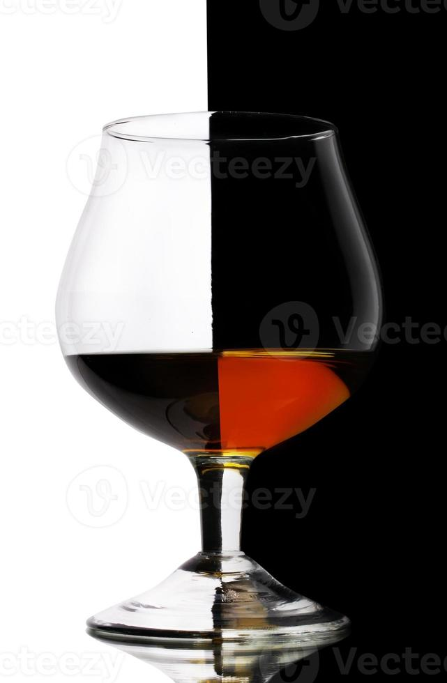 Glass of cognac on white-black background photo