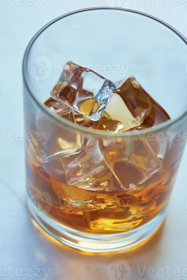 whisky con hielo en una mesa foto