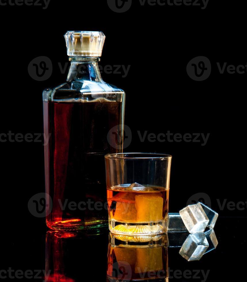 botella y vaso de whisky con hielo foto