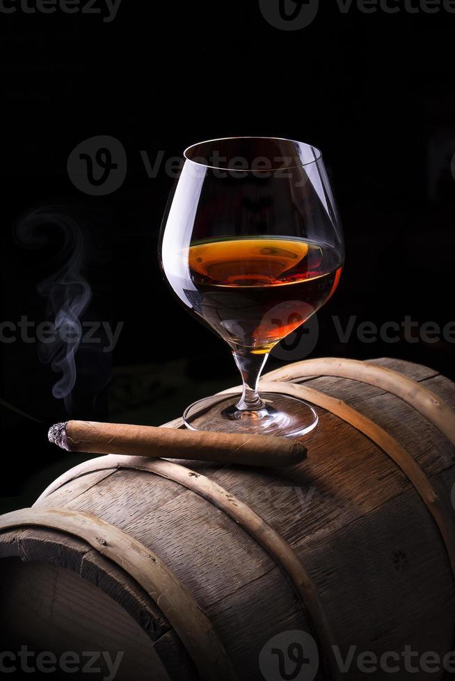coñac y cigarro en negro con barril vintage foto