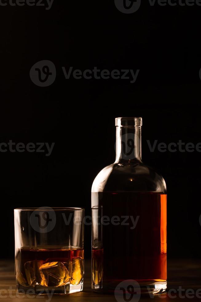 Vaso de whisky con hielo y botella en mesa de madera. foto