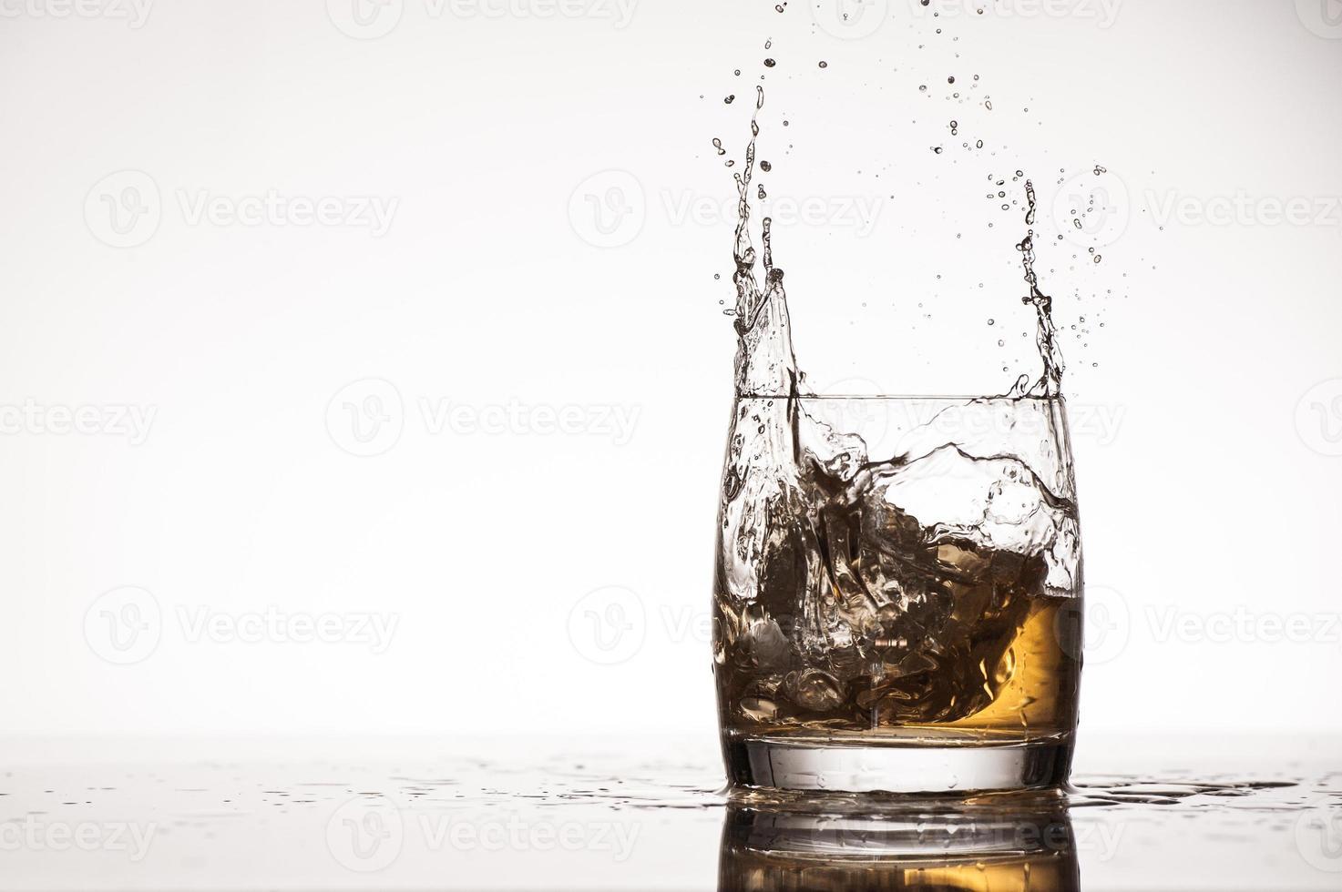 salpicaduras de hielo en whisky o brandy foto
