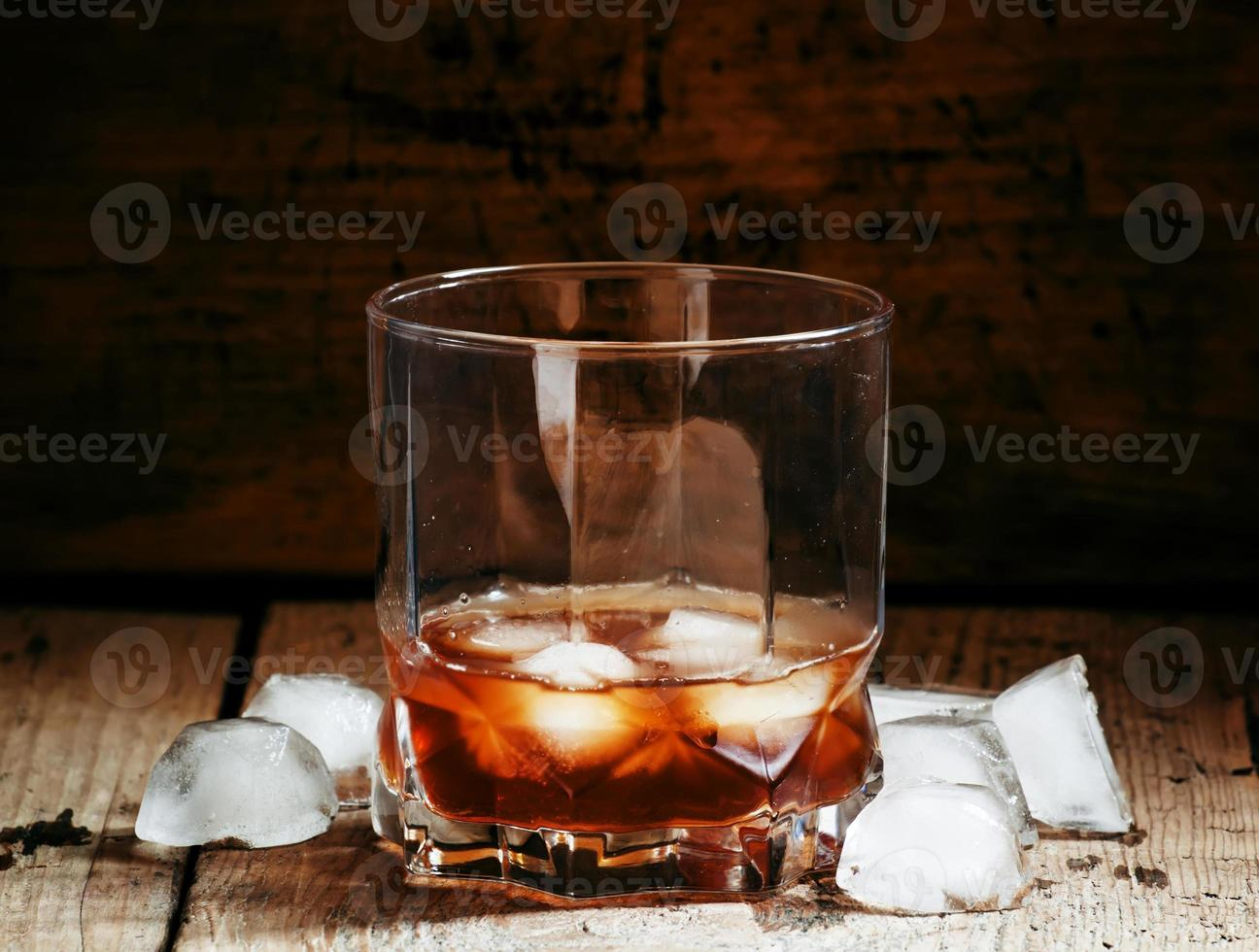 Cold whiskey with ice in a dark cellar photo