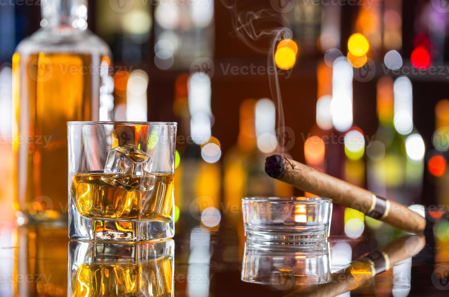 Whiskey drink with smoking cigar on bar photo