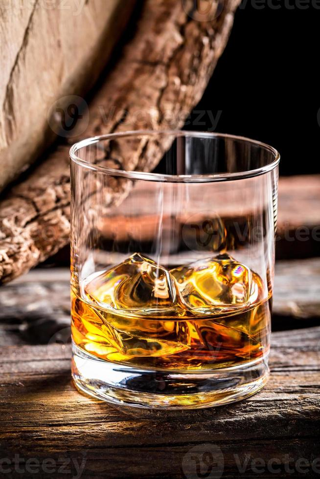 Glass of whisky and old oak barrel photo