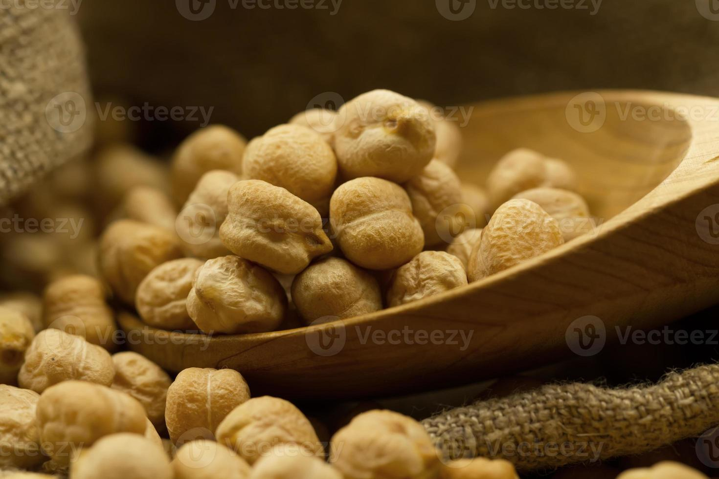 scattered chickpeas from jute bag on old wooden background photo
