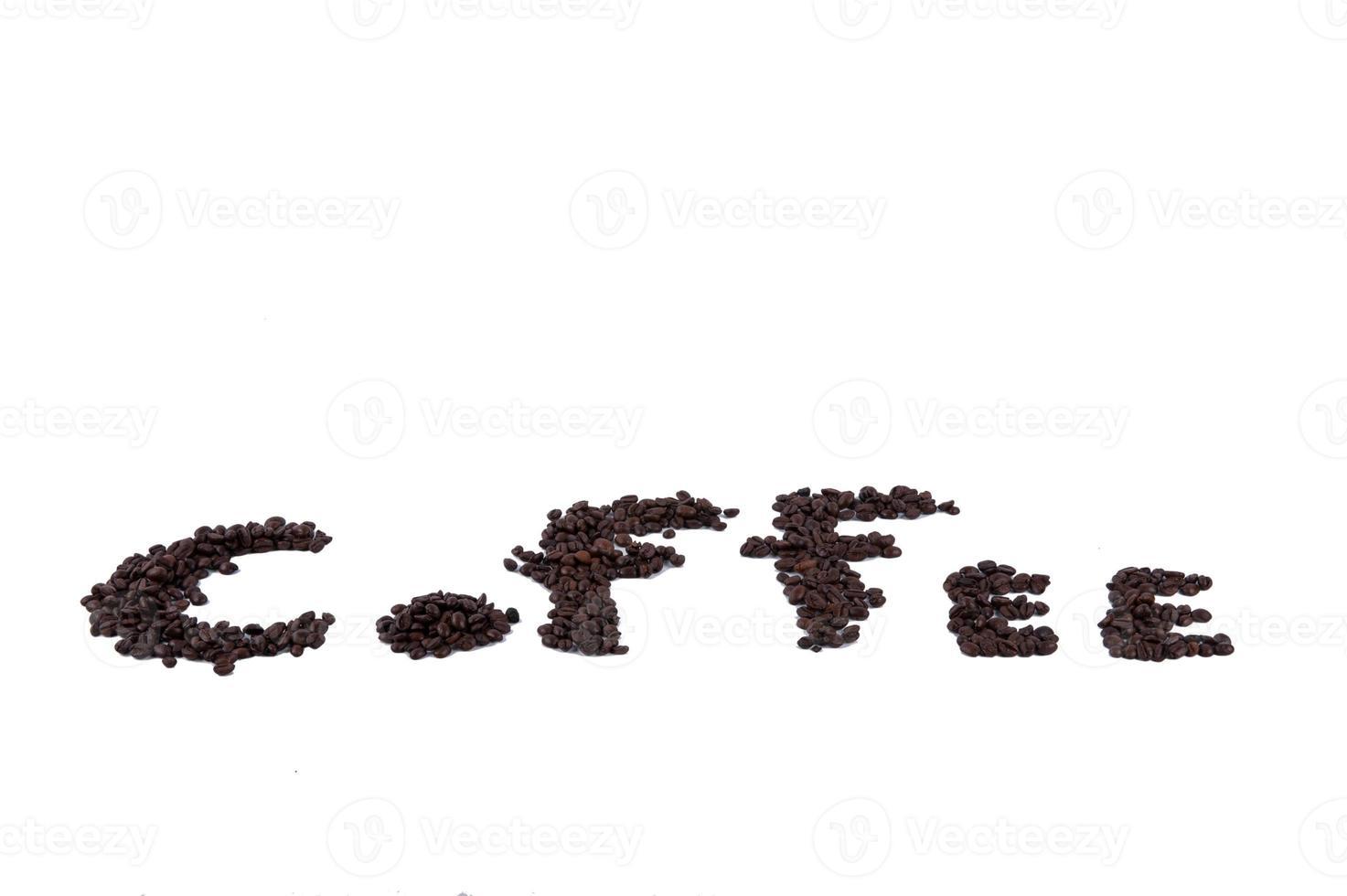 Los granos de café tostado se amontonan desde la parte superior sobre fondo blanco. foto