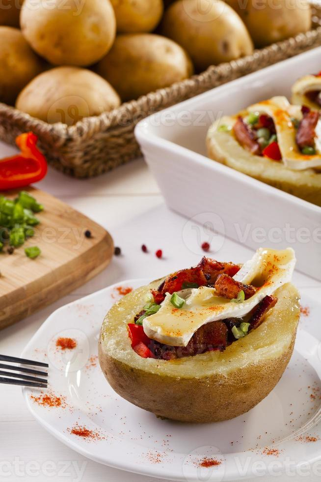 Baked potatoes stuffed with bacon, served with camembert photo