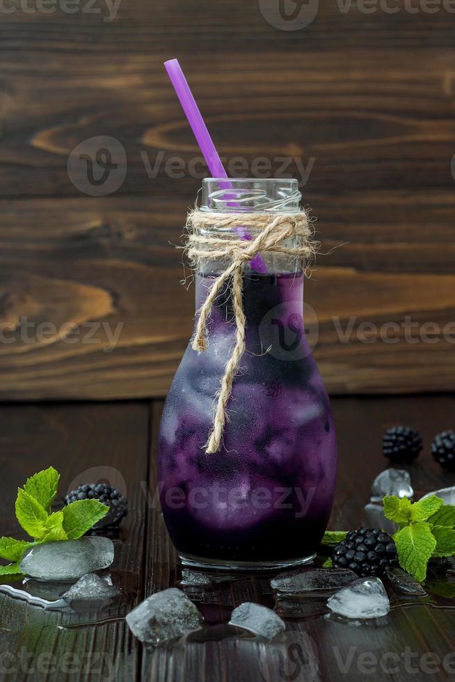 refrescante jugo de mora en una botella vintage de estilo ecológico foto