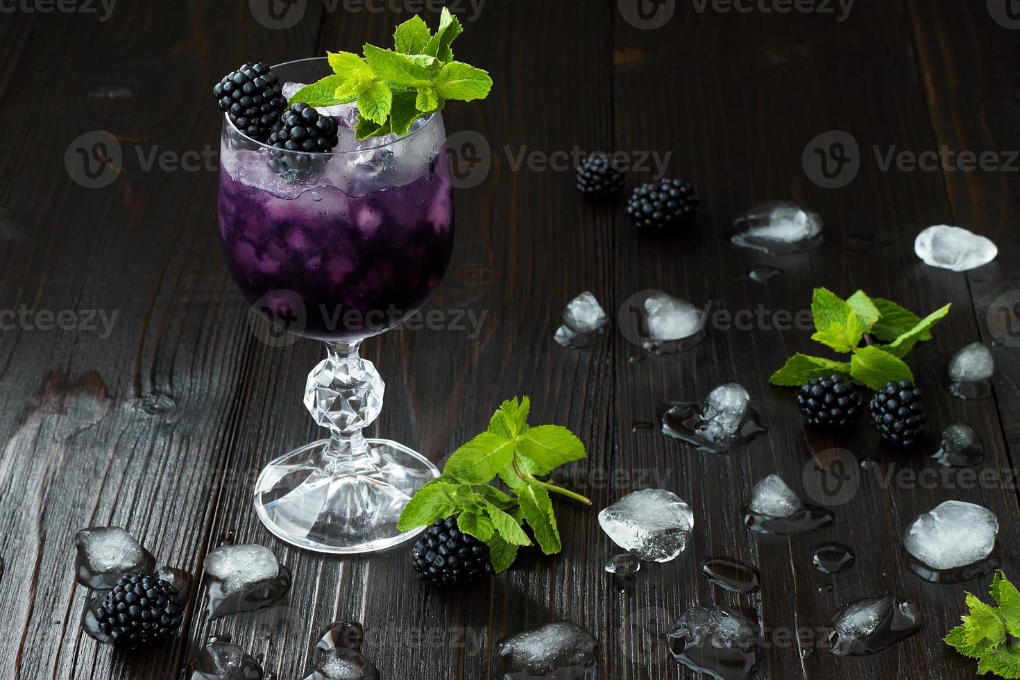 cóctel de moras en copa de vino con menta y hielo foto