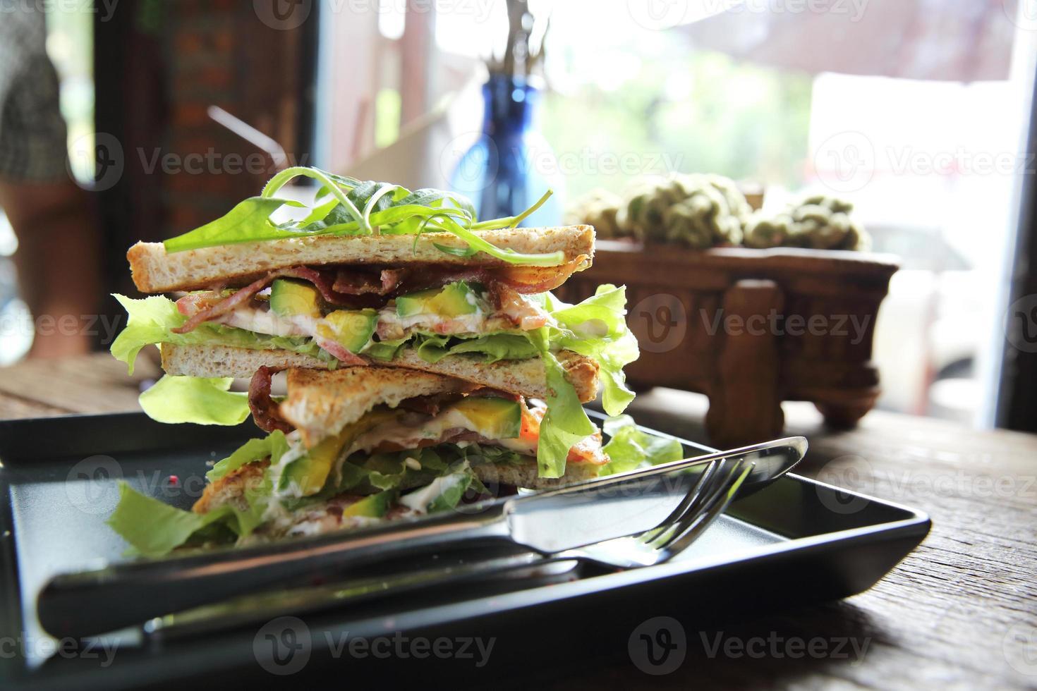 sanduíches com encontro e legumes em fundo madeira foto
