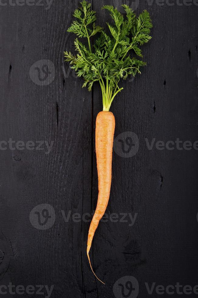 Carrot with green leaves over wooden background. Vegetable. Food photo