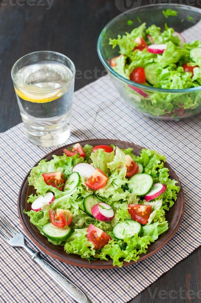 Tomato and cucumber salad with lettuce leafes photo