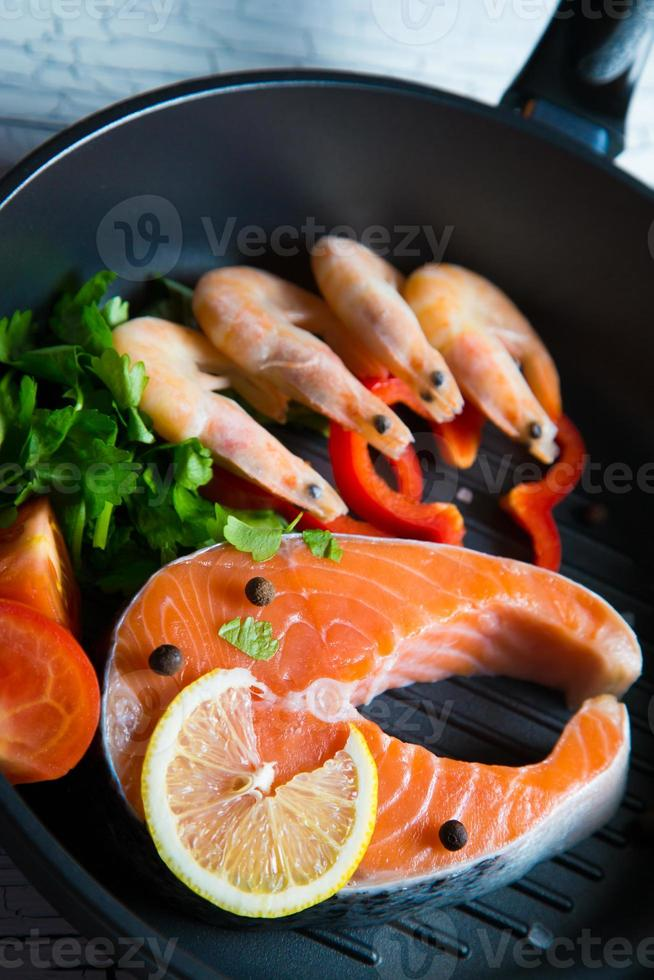 Fresh salmon steak in a pan grilled shrimp and vegetables photo